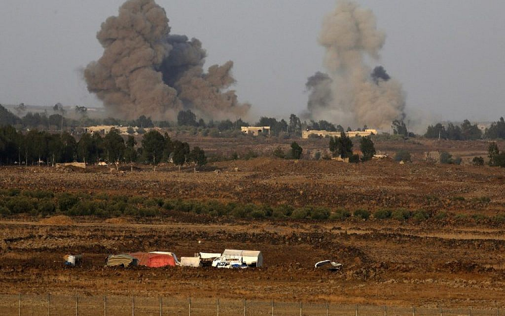 A picture taken on July 24, 2018 from the Tal Saki hill in the Golan Heights shows smoke rising above buildings across the border in Syria during air strikes backing a Syrian-government-led offensive in the southwestern province of Daraa. (AFP/ JALAA MAREY)