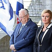 Israeli President Reuven Rivlin, left, and Croatian President Kolinda Grabar Kitarovic pay a tribute at the memorial in the shape of a flower for the victims killed at the Jasenovac concentration camp which was dismantled 73 years ago in Jasenovac, on July 25, 2018.  (AFP/STRINGER)