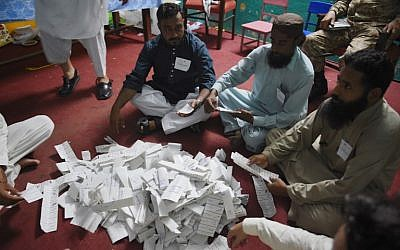 Pakistani election officials count ballots after polls closed at a polling station in Rawalpindi on July 25, 2018. (AFP Photo/Farooq Naeem)
