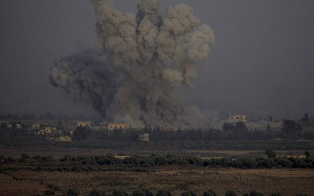 A picture taken on July 25, 2018 from the Tal Saki hill in the Golan Heights shows smoke rising above buildings across the border in Syria during air strikes backing a Syrian-government-led offensive in the southern province of Quneitra. (AFP / JALAA MAREY)