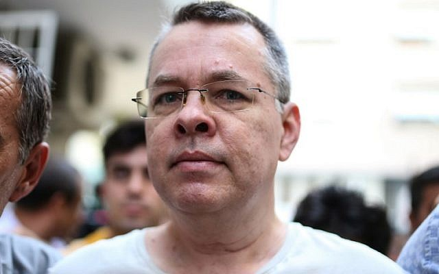 US pastor Andrew Craig Brunson escorted by Turkish plain clothes police officers arrives at his house on July 25, 2018 in Izmir. (AFP PHOTO)