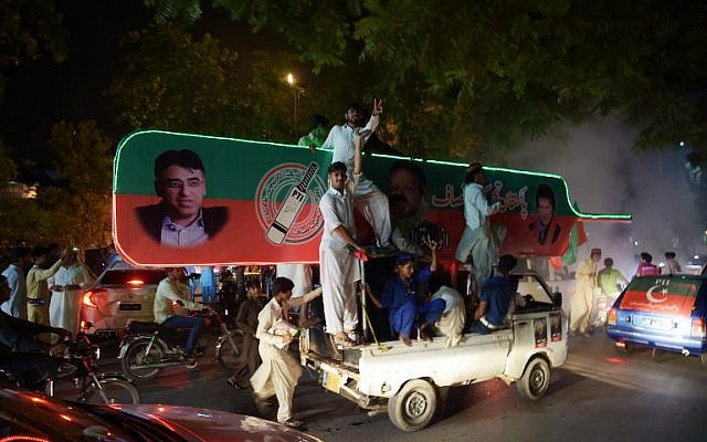 Supporters of Pakistan's cricketer-turned politician Imran Khan, head of the Pakistan Tehreek-e-Insaf (Movement for Justice) party, celebrate on a street during general election in Islamabad on July 25, 2018. (AFP/AAMIR QURESHI)