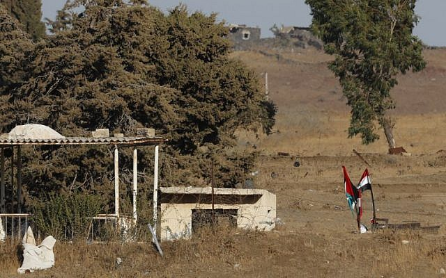 A picture taken on July 26, 2018, near Kibbutz Ein Zivan in the Israeli Golan Heights, shows Syrian national flags (R) and the Baath party flag (L) flying across the border as regime forces retake the area from rebels. (AFP Photo/Jack Guez)