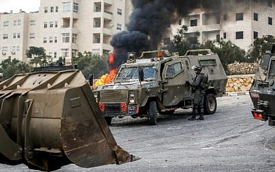 IDF vehicles deploy during clashes in the village of Kobar, west of Ramallah in the West Bank on July 27, 2018, where a Palestinian stabbing attacker left from the previous night towards the Adam settlement. ( AFP PHOTO / ABBAS MOMANI)