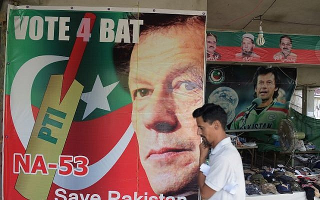 A man walks past a poster of Pakistan's cricketer-turned politician Imran Khan, and head of the Pakistan Tehreek-e-Insaf (Movement for Justice) party, at a market in Islamabad on July 27, 2018. (AFP/Aamir Qureshi)