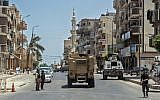 Egyptian policemen driving on a road leading to the North Sinai provincial capital of El-Arish, July 26, 2018. (AFP/Khaled DESOUKI)