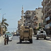 A picture taken on July 26, 2018, shows Egyptian policemen driving on a road leading to the North Sinai provincial capital of El-Arish.  (AFP PHOTO / Khaled DESOUKI)