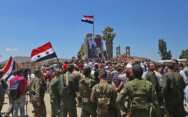 Syrian troops raise the Syrian flag in the border town of Quneitra in the Syrian Golan Heights on July 27, 2018. (AFP Photo/Youssef Karwashan)