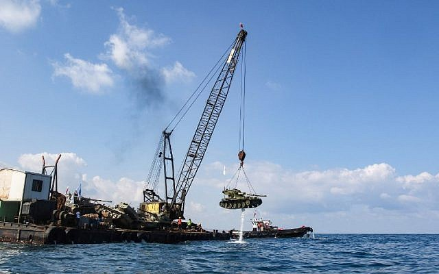 Environmental activists drop off an old battle tank provided by the Lebanese Armed Forces into the Mediterranean Sea, about three kilometres off the coast of the southern Lebanese port city of Sidon, on July 28, 2018, to create new habitat for marine life. ( AFP PHOTO / Mahmoud ZAYYAT)