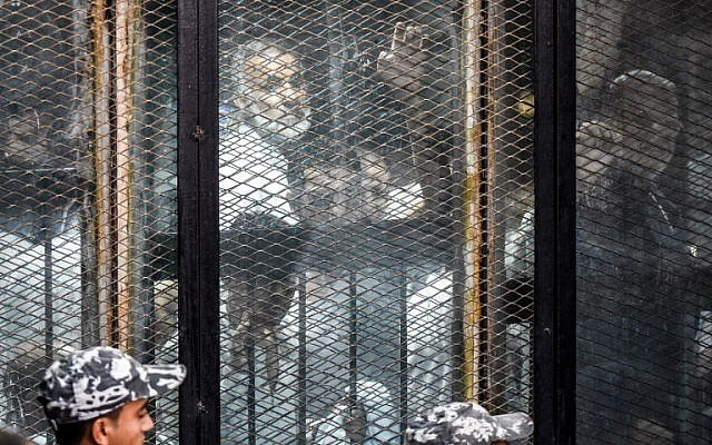 Essam el-Erian (R), one of the highest-ranking leaders of Egypt's banned Muslim Brotherhood, is seen alongside other members of the group inside a glass dock during their trial in the capital Cairo on July 28, 2018. (AFP Photo/Khaled Desouki)