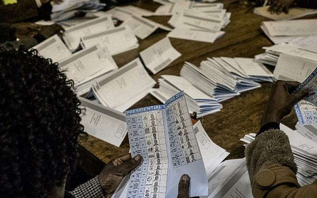 Election officials tally ballots during counting operations for Zimbabwe's general election at the David Livingston Primary school in central Harare on July 30, 2018. (AFP Photo/Marco Longari)