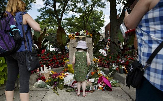 A young girl stands at the foot of a makeshift memorial where people are adding flowers to honor and remember the victims of Sunday night's mass shooting on July 24, 2018 in Toronto, Canada. (Cole Burston/Getty Images/AFP)