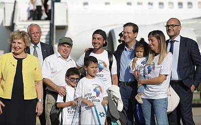 Outgoing Jewish Agency head Nathan Sharansky (3rd left) and new chief Isaac Herzog (4th right) welcome new immigrants on a special 'aliyah' flight organized by the Jewish Agency, at Ben Gurion airport on July 23, 2018 (Jewish Agency Facebook page/Dudi Salem, Zoog Productions)