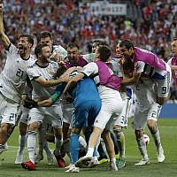Russian players mob Russia goalkeeper Igor Akinfeev, front left in blue, after Russia defeated Spain by winning a penalty shoot in the round of 16 match between Spain and Russia at the 2018 soccer World Cup at the Luzhniki Stadium in Moscow, Russia, July 1, 2018. (AP Photo/Manu Fernandez)