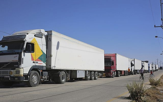 Trucks laden with aid for displaced Syrians wait to cross from Jordan to the Syrian side of the border, in Jabir As Sirhan, Jordan, Sunday, July 1, 2018.  (AP Photo/Omar Akour)