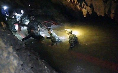 In this handout photo released by Tham Luang Rescue Operation Center, Thai rescue teams walk inside cave complex where 12 boys and their soccer coach went missing, in Mae Sai, Chiang Rai province, in northern Thailand, on July 2, 2018. (Tham Luang Rescue Operation Center via AP)