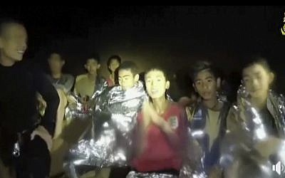In this July 3, 2018, image taken from video provided by the Thai Navy Seal, Thai boys are with Navy SEALs inside the cave, Mae Sai, northern Thailand. (Thai Navy Seal via AP)