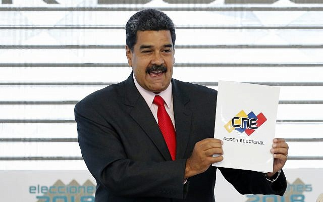 In this May 22, 2018, photo, Venezuela's President Nicolas Maduro holds up the National Electoral Council certificate declaring him the winner of the presidential election, during a ceremony at CNE headquarters in Caracas, Venezuela. (AP Photo/Ariana Cubillos)