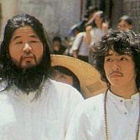 In this undated file photo, cult guru Shoko Asahara, left, of Aum Shinrikyo walks with Yoshihiro Inoue, then a close aid, in Tokyo. (Kyodo News via AP)