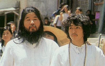 In this undated file photo, cult guru Shoko Asahara, left, of Aum Shinrikyo walks with Yoshihiro Inoue, then a close aid, in Tokyo. (Kyodo News via AP)