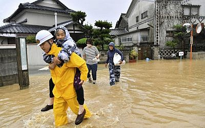Residents are evacuated to a safer place from floodwaters caused by heavy rains in Kurashiki, Okayama prefecture, southwestern Japan, Saturday, July 7, 2018. Torrents of rainfall and flooding continued to batter southwestern Japan. (Koki Sengoku/Kyodo News via AP)