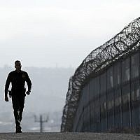 In this June 22, 2016, file photo, Border Patrol agent Eduardo Olmos walks near the secondary fence separating Tijuana, Mexico, background, and San Diego in San Diego (AP Photo/Gregory Bull, File)