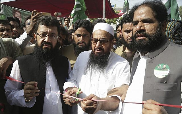In this Sunday, July 8, 2018 photo, Hafiz Saeed, center, head of the Pakistani religious group Jamaat-ud-Dawa inaugurates an election office of the newly formed political party Allah-o-Akbar Tehreek, in Lahore, Pakistan (AP Photo/K.M. Chaudary)