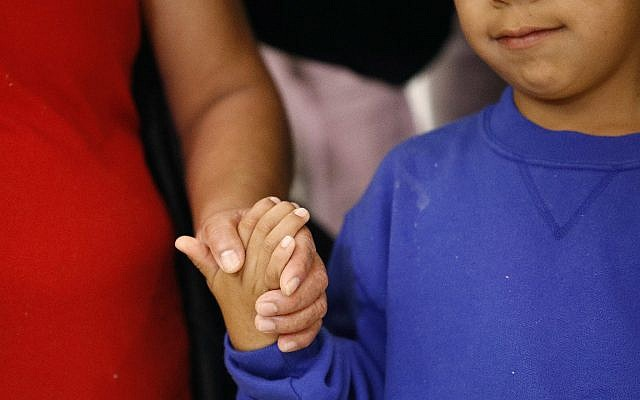In this June 22, 2018, file photo, a mother, left, and son, from Guatemala, hold hands during a news conference following their reunion in Linthicum, Maryland, after being reunited following their separation at the US border. (AP Photo/Patrick Semansky, File)