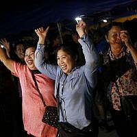 People celebrate after divers evacuated some of the 12 boys and their coach who were trapped at Tham Luang cave in the Mae Sai district of Chiang Rai province, northern Thailand, July 10, 2018. (AP Photo/Sakchai Lalit)