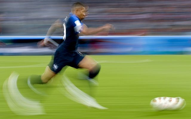 In this photo taken with slow shutter speed France's Kylian Mbappe runs with the ball during the semifinal match between France and Belgium at the 2018 soccer World Cup in the St. Petersburg Stadium, in St. Petersburg, Russia on July 10, 2018. (AP Photo/Petr David Josek)
