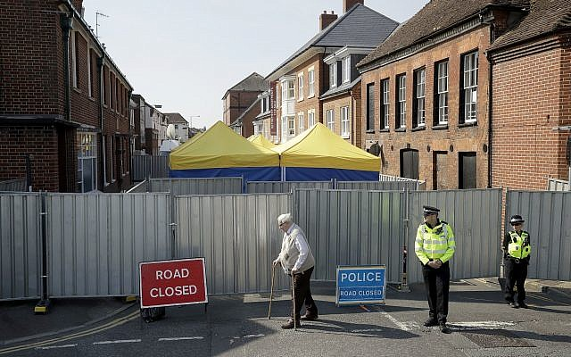 In this Friday, July 6, 2018 file photo, an elderly man walks by as British police officers guard metal fencing surrounding tents set up by search teams at the end of Rollestone Street, outside the location of the John Baker House for homeless people in Salisbury, England. British detectives investigating the poisoning of two people by the nerve agent Novichok in southern England said Friday, July 13, 2018 that scientists have found the source of the deadly substance. (AP Photo/Matt Dunham)