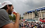 A man drinks a beer in a Budweiser pavilion in front of the Lenin statue and the Luzhniki Stadium as fans arrive for the semifinal match between Croatia and England, during the 2018 soccer World Cup in Moscow, Russia, July 11, 2018 . (Rebecca Blackwell/AP)