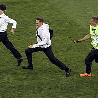 A steward runs after two members of Pussy Riot who invaded the pitch during the final match between France and Croatia at the 2018 soccer World Cup in the Luzhniki Stadium in Moscow, Russia, July 15, 2018. (AP Photo/Thanassis Stavrakis)