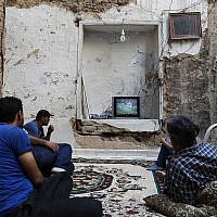 Syrians watch the World Cup soccer final match between France and Croatia at their home, that was partially destroyed by the war leaving two of its rooms without a ceiling, in the town of Ain Terma, in the Eastern Ghouta suburb of Damascus, Syria, July 15, 2018. (AP Photo/Hassan Ammar)