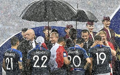FIFA President Gianni Infantino, Russian President Vladimir Putin, French President Emmanuel Macron and Croatian President Kolinda Grabar-Kitarovic, from left, stand in the puring rain as they congratulate the French players after France won 4-2 in the final match between France and Croatia at the 2018 soccer World Cup in the Luzhniki Stadium in Moscow, Russia, Sunday, July 15, 2018. (AP Photo/Martin Meissner)