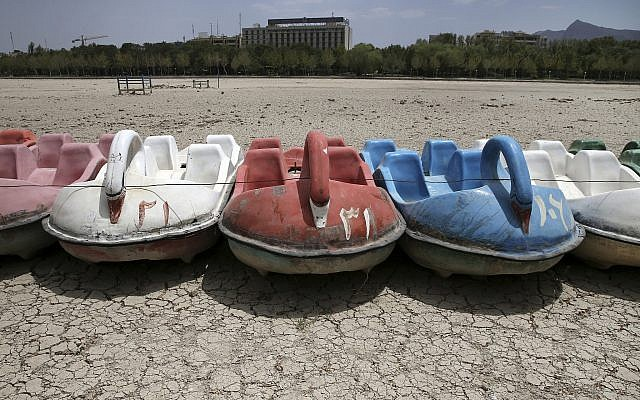 In this Tuesday, July 10, 2018 photo, paddle boats sit on the parched Zayandeh Roud riverbed, in Isfahan, Iran. (AP Photo/Vahid Salemi)