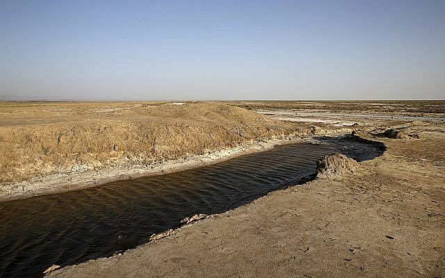 This Tuesday, July 10, 2018 photo shows one of the last puddles of salty water remaining in the Gavkhouni wetlands, which was once a swamp fed by the Zayandeh Roud river, and is now surrounded by desiccated salt-laced fields, outside the town of Varzaneh and its suburbs, home to 30,000 people some 550 kilometers (340 miles) south of the capital Tehran, Iran. (AP Photo/Vahid Salemi)