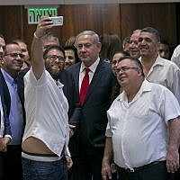 Likud MK Oren Hazan takes a selfie with Prime Minister Benjamin Netanyahu, center, and MK David Bitan, right of Netanyahu, after the passage of the nation-state law at the Knesset on July 19, 2018. (AP Photo/Olivier Fitoussi)
