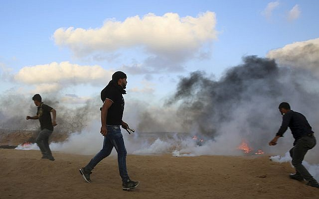 Protesters try to throw back teargas canisters fired by Israeli troops near the fence of the Gaza Strip border with Israel, during a protest east of Khan Younis, southern Gaza Strip, Friday, July 20, 2018 (AP Photo/Adel Hana)