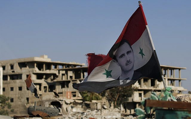 A Syrian national flag with the picture of the Syrian President Bashar Assad hangs at an Army check point, in the town of Douma in the eastern Ghouta region, near the Syrian capital Damascus, Syria, July 15, 2018. (AP Photo/Hassan Ammar)