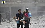 Civil defense workers known as the White Helmets carrying children after airstrikes hit a school housing a number of displaced people, in the western part of the southern Daraa province of Syria,  June 14, 2017. (Syrian Civil Defense White Helmets via AP)