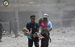 In this Wednesday, June 14, 2017, file photo, provided by the Syrian Civil Defense group known as the White Helmets, shows civil defense workers carrying children after airstrikes hit a school housing a number of displaced people, in the western part of the southern Daraa province of Syria. (Syrian Civil Defense White Helmets via AP)