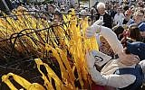 Participants place yellow ribbons with Jewish names on a barbed wire fence during a march that marks 76 years since first deportations from the Warsaw Ghetto and honors Jewish activist Szmul Zygielbojm, who committed suicide in 1943 in protest against the world's indifference to Holocaust, at Umschagplatz Monument in Warsaw, Poland, Sunday, July 22, 2018.(AP Photo/Czarek Sokolowski)
