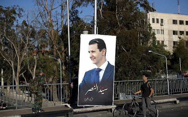 "Syrians pass by a poster of President Bashar Assad with Arabic that read, ""Master of victory,"" hangs on a bridge in the Syrian capital Damascus, Syria, July 14, 2018. (Hassan Ammar/AP)"