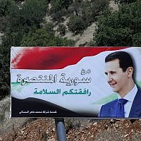 """A poster of Syrian President Bashar Assad with Arabic that reads """"Welcome in victorious Syria,"""" is displayed on the border between Lebanon and Syria, July 20, 2018. (Hassan Ammar/AP)"""