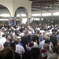 In this photo released by the Syrian official news agency SANA, mourners from the Druze community attend a mass funeral of people killed a day earlier by a series of suicide bombings launched by the Islamic State's fighters on the eastern and northern countryside of the southern province of al-Sweida, Syria, Thursday, July 26, 2018. (SANA via AP)