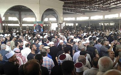 In this photo released by the Syrian official news agency SANA, mourners from the Druze community attend a mass funeral of people killed a day earlier by a series of suicide bombings launched by the Islamic State's fighters on the eastern and northern countryside of the southern province of al-Sweida, Syria, on July 26, 2018. (SANA via AP)