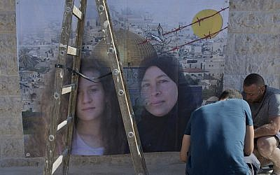 Palestinians hang a poster showing Nariman Tamimi, right, and her daughter Ahed, during preparations for their upcoming release from an Israeli prison after serving an eight month sentence, at the family house in the West Bank village of Nebi Saleh, west of Ramallah, July 28, 2018. (AP Photo/Nasser Nasser)