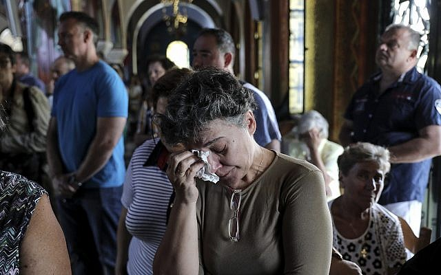 Greek Orthodox faithful attend a memorial service for the victims of a forest fire, inside a church at Mati village, east of Athens, July 29, 2018. (AP Photo/Yorgos Karahalis)