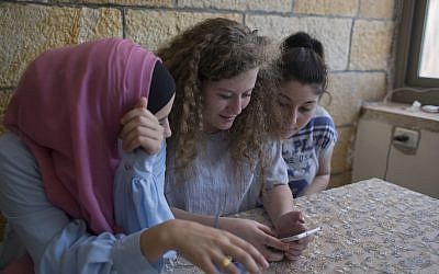 Ahed Tamimi, center, surfs the internet with her friends at the family house in the West Bank village of Nebi Saleh, near Ramallah, Monday, July 30, 2018. (AP Photo/Nasser Nasser)